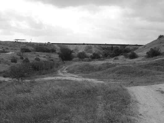 מבט על הגשר מצפון. נראית גם סוללת העפר ששימשה באופן זמני למעבר הרכבת. מצד שמאל דגל ישראל. זאת האנדרטה לסיירת שקד.